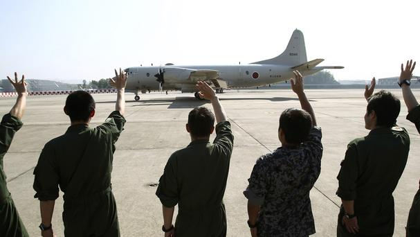 Ground crew members wave to a Japanese Maritime Defence Force P3C patrol plane as it heads for Australia to join a search-and-rescue operation for the missing Malaysia Airlines flight MH370 (AP)