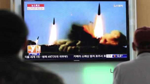 People in Seoul watch a TV news programme showing rockets launched by North Korea (AP)