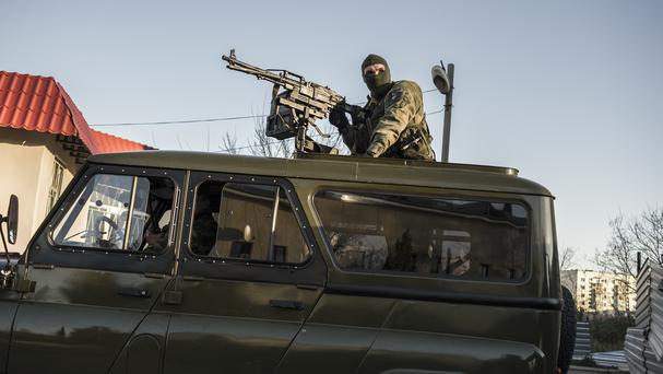 A Russian machine gunner controls the gate of the Belbek airbase, outside Sevastopol, Crimea (AP)