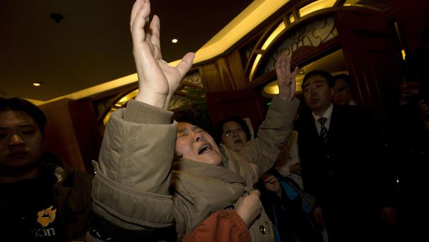 Relatives in Beijing grieve after being told of the latest news (AP)