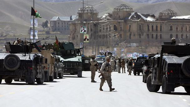 Afghan security officers arrive to the scene after two suicide bombers struck near the home of a candidate running for president (AP)