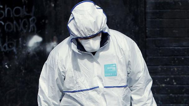 A member of the Garda forensics team at the scene on Fassaugh Avenue, Cabra, north Dublin, where a man was found seriously injured outside the Cabra House pub.