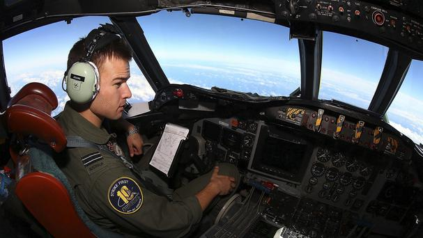 Flt Lt Russell Adams looks out from the cockpit of a Royal Australian Air Force Orion during a search for the missing Malaysia Airlines Flight 370 (AP)
