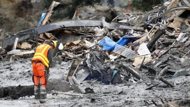 A worker searches debris at the scene of a deadly mudslide in Washington state in the US (AP/Rick Wilking)