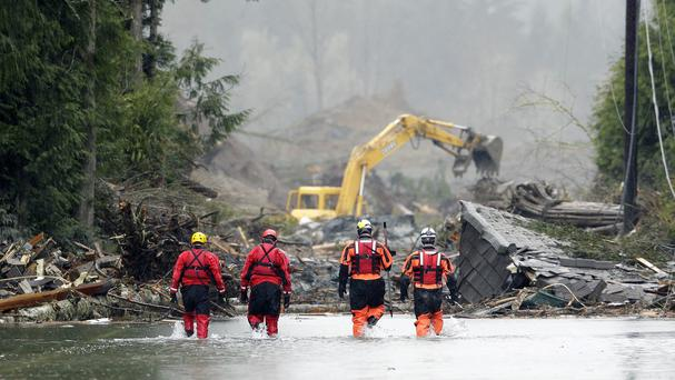 Search and rescue workers wade through water covering Washington Highway 530 on the eastern edge of the massive mudslide (AP)