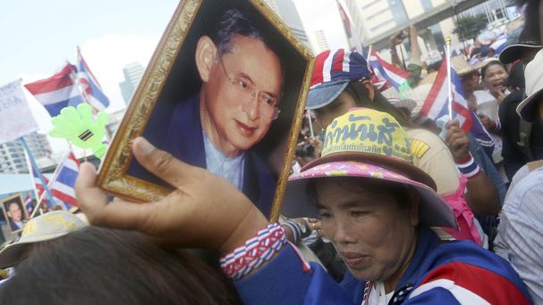 A Thai anti-government protester holds a portrait of King Bhumibol Adulyadej as she joins a mass rally in Bangkok (AP)