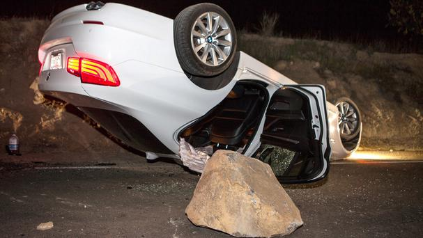 A car sits overturned on a highway in the Carbon Canyon area of Brea, California, after hitting a rockslide caused by an earthquake. The people inside the car sustained minor injuries. A magnitude-5.1 earthquake centred near Los Angeles (AP)