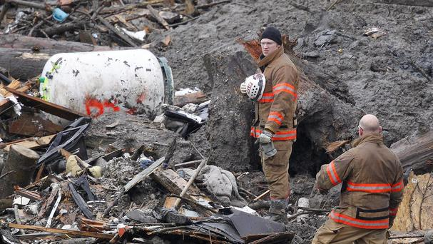 Searchers pause for a moment of silence at the scene of the deadly Washington mudslide (AP)