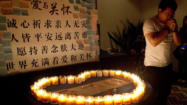 A relative of one of the Chinese passengers onboard Malaysia Airlines Flight 370 prays near candles before a briefing with Malaysian officials at a hotel in Beijing (AP)