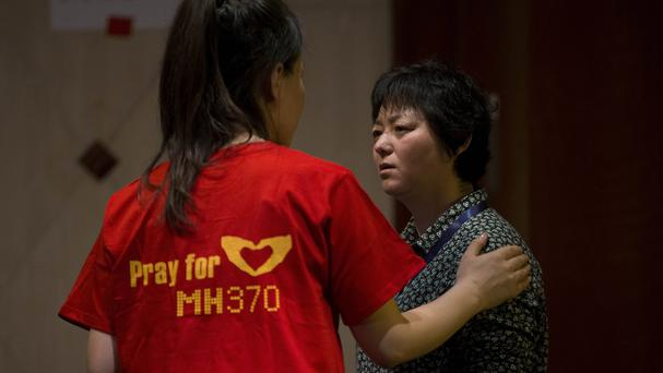 Relatives of Chinese passengers aboard the missing Malaysia Airlines flight MH370 comfort each other before a daily briefing held by Malaysian officials (AP)