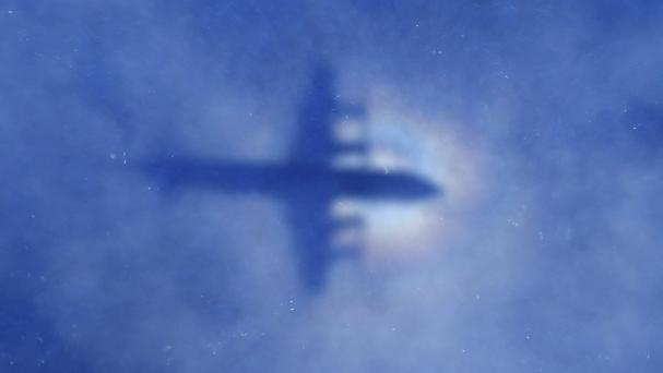 The shadow of a Royal New Zealand Air Force P-3 Orion aircraft is seen on low cloud cover while it searches for the missing jet (AP)