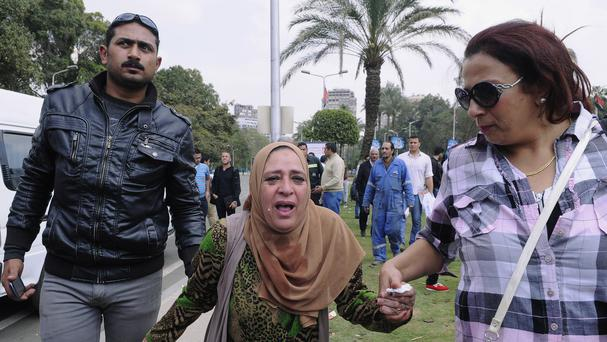 An Egyptian woman, centre, is escorted out of the site of multiple bombings outside the main campus of Cairo University in Giza (AP)