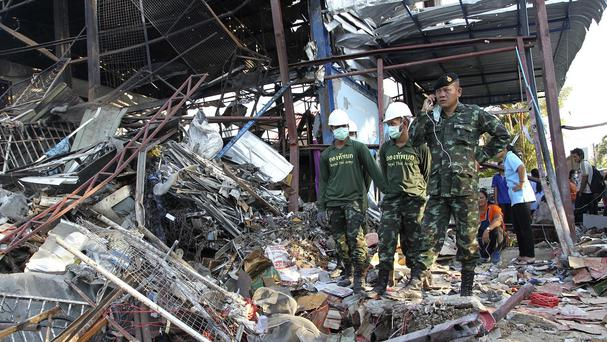 Soldiers stand next to a crater created by a bomb explosion at a scrap shop in Bangkok which killed seven people (AP)
