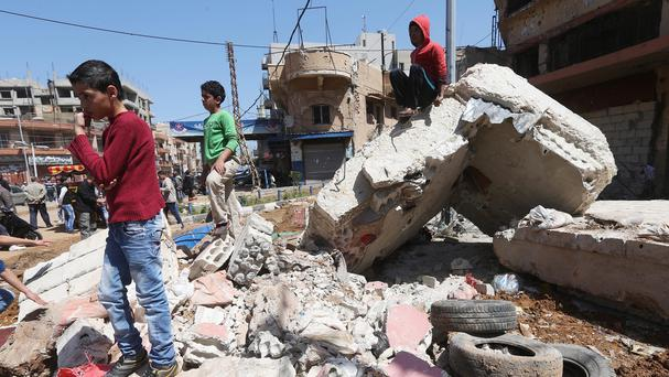 Lebanese boys on the debris of a destroyed cement barrier that was used by Sunni fighters (AP)