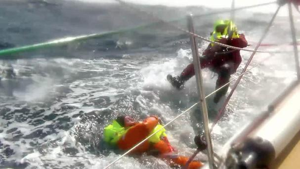 Sailor Andrew Taylor, left, being rescued by Jason Middleton (right) from the Pacific Ocean after falling overboard (Clipper Ventures/AP)