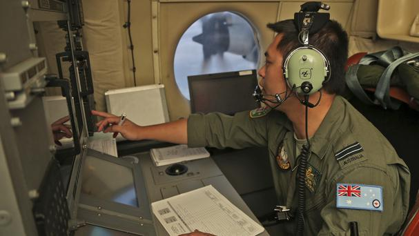Flight Officer Jack Chen mans the navigation and comms station onboard a Royal Australian Air Force P-3 Orion during the search for missing flight MH370 (AP)