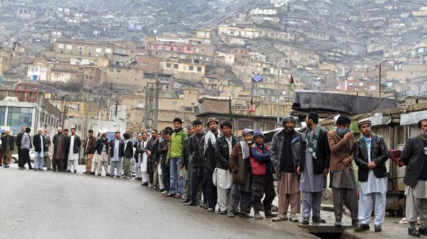 Afghan men queue outside a polling station to cast their ballots in Kabul (AP)