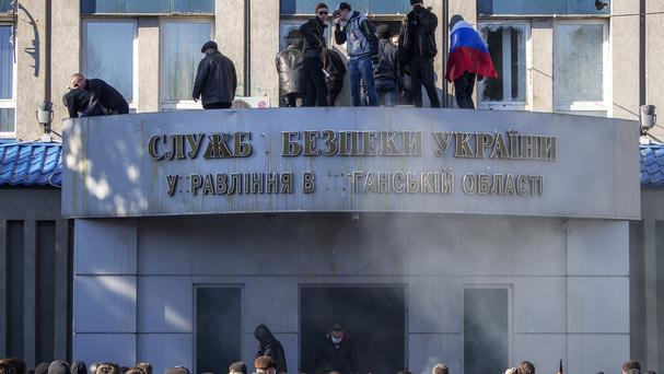 Pro-Russian activists stand on the balcony of the Ukrainian regional office of the Security Service in Luhansk, Ukraine (AP)