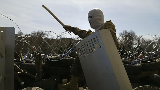 A masked man stands on top of a barricade at the regional administration building in Donetsk, Ukraine (AP)