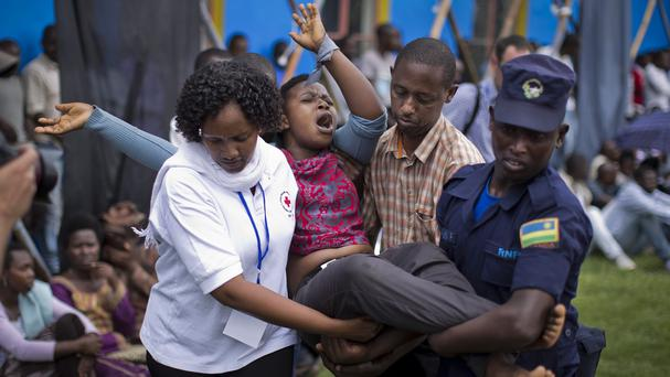 A distraught woman, one of dozens overcome by grief at recalling the horror of the genocide, is carried away to receive help during a public ceremony to mark the 20th anniversary of the Rwandan genocide in Kigali (AP)