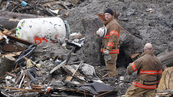 Searchers pause for a moment of silence at the scene of the mudslide in Washington state (AP)
