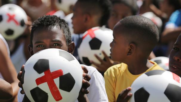 Boys hold footballs painted with a red cross during protest against the money spent on the World Cup 2014