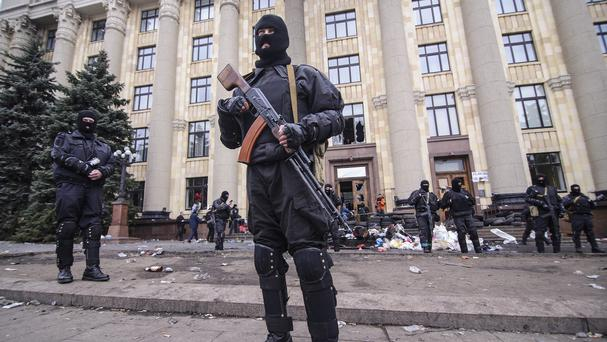 Members of a special police unit guard the regional administration building in Kharkiv, Ukraine