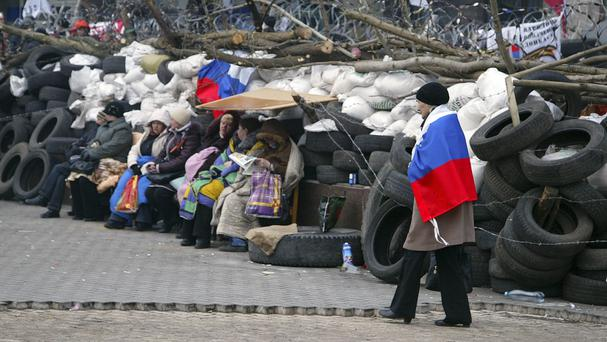 A woman wrapped in a Russian national flag walks in front of a barricade at the regional administration building in Donetsk, Ukraine. (AP)