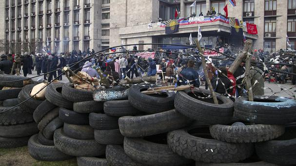 People gather in front of a barricade at the regional administration building in Donetsk, Ukraine. (AP)