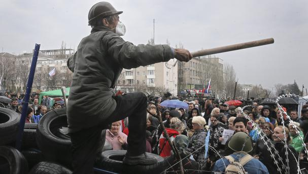 A masked pro-Russian activist speaks to supporters as he stands atop a barricade during a rally at the regional administration building in Donetsk (AP)