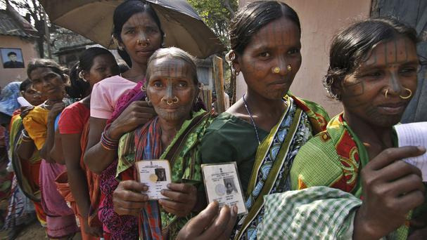 Indigenous women belonging to the Kandha tribe display their voter's identity cards outside a polling station in Orissa state (AP)