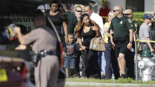 Parents and children are escorted away by police after a deadly crash at a Florida day care centre (AP)