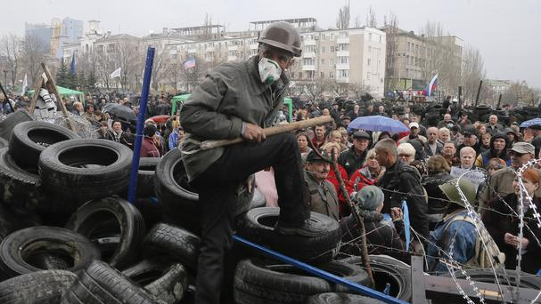A pro-Russian activist guards a barricade during a rally at the regional administration building in Donetsk (AP)