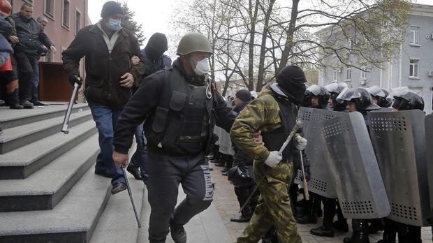 Masked pro-Russian activists leave the regional prosecutor's office in Donetsk (AP)
