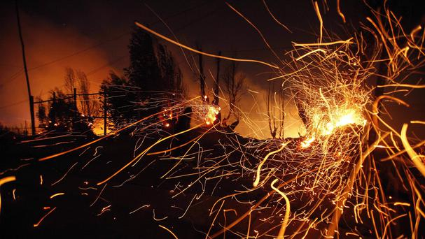 Sparks fly carried by the wind as a large forest fire reaches urban areas in Valparaiso, Chile. (AP)