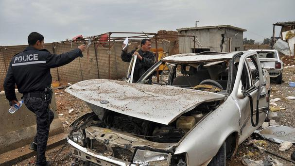 Iraqi security forces inspect the site of a suicide car bombing in the northern town of Dibis. (AP)
