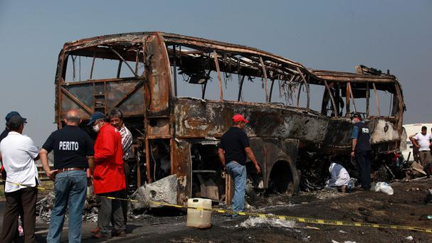 Forensic experts inspect the site of the bus crash in Veracruz, Mexico, which led to dozens of deaths (AP)