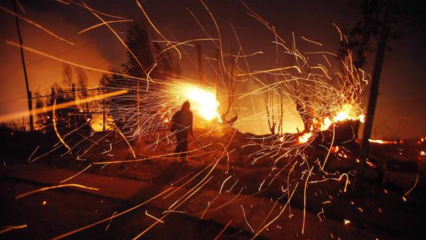 Sparks fly as the forest fire in Valparaiso, Chile, rages (AP)