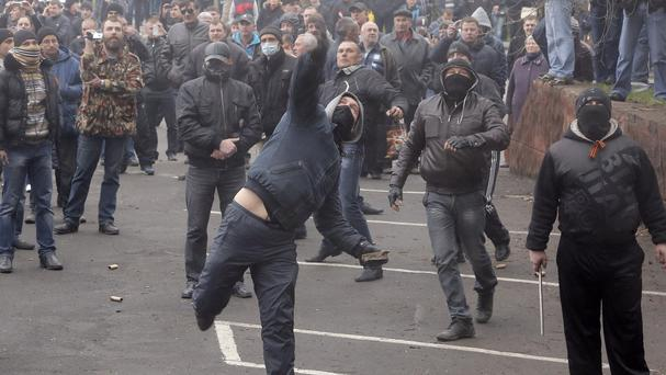 Pro-Russian men throw stones during the mass storming of a police station in the eastern Ukrainian town of Horlivka (AP)
