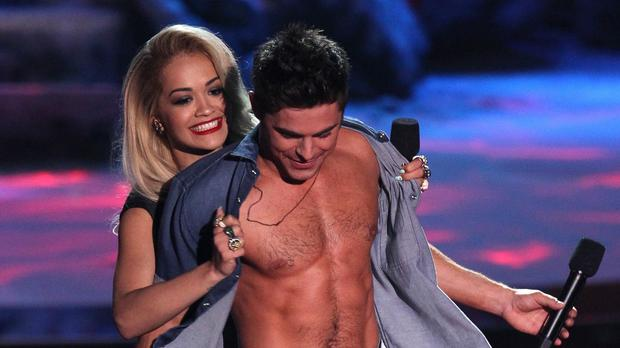 Rita Ora rips open Zac Efron's shirt as he accepts the award for best shirtless performance for That Awkward Moment at the MTV Movie Awards. (Matt Sayles/Invision/AP)
