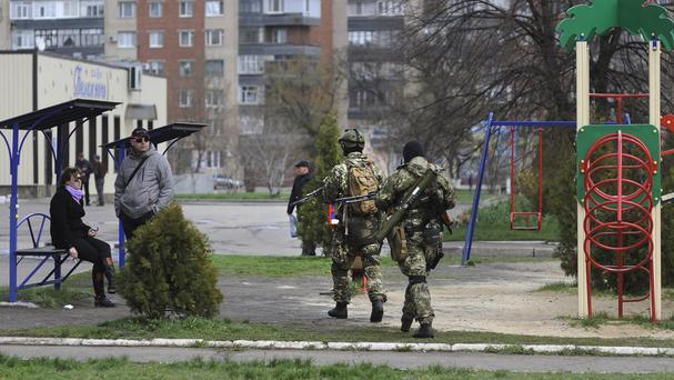 Armed pro-Russian activists walk through a playground near the seized Ukrainian regional administration building in the eastern Ukrainian town of Slovyansk. (AP)