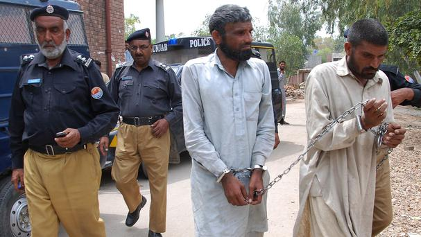 Police officers escort Farman Ali, right, and Arif Ali, two brothers suspected of cannibalism, to a local court in Sargodha, Pakistan (AP)