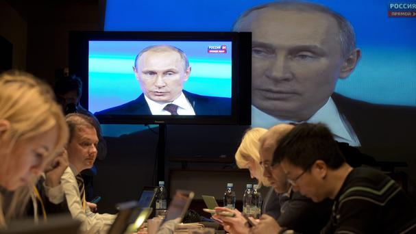 Reporters listen to Russian President Vladimir Putin during a nationwide phone-in (AP)