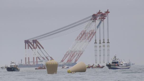 Cranes wait near the buoys installed to mark the sunken ferry Sewol in the water off the southern coast near Jindo, South Korea (AP)