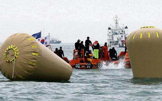 A diver jumps in near the buoys installed to mark the sunken ferry Sewol