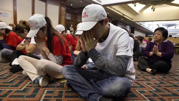Relatives of Chinese passengers on board the Malaysia Airlines Flight 370 pray at a hotel conference room in Beijing (AP)