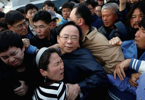 South Korean Minister of Oceans and Fisheries Lee Ju-young (centre) struggles with angry family members of the missing passengers who were on the capsized Sewol passenger ship, which sank in the sea off Jindo