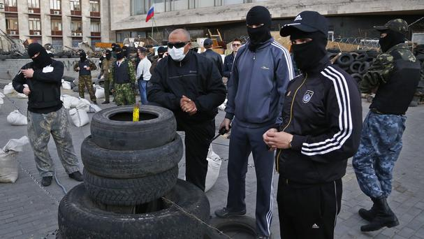 Masked pro-Russia protesters guard barricades at the regional administration building that they had seized earlier in Donetsk, eastern Ukraine (AP)