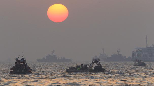 The sun begins to set above searchers and divers looking for bodies of passengers believed to have been trapped in the sunken ferry Sewol in the water off the southern coast near Jindo, south of Seoul (AP)