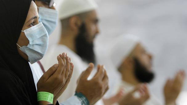 Pilgrims, some wearing masks as a precaution against the Middle East respiratory syndrome, pray in Mina near the Muslim holy city of Mecca, Saudi Arabia (AP)